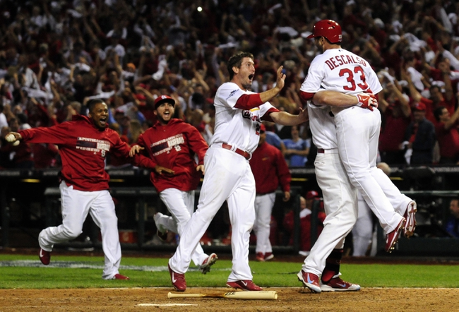 Oct 11, 2013; St. Louis, MO, USA; St. Louis Cardinals shortstop Daniel Descalso (33) celebrates with left fielder Matt Holliday (7) and third baseman David Freese (23) after scoring the winning run in the 13th inning against the Los Angeles Dodgers in game one of the National League Championship Series baseball game at Busch Stadium. Mandatory Credit: J