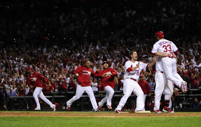 Oct 11, 2013; St. Louis, MO, USA; St. Louis Cardinals shortstop Daniel Descalso (33) celebrates with left fielder Matt Holliday (7) and third baseman David Freese (23) after scoring the winning run in the 13th inning against the Los Angeles Dodgers in game one of the National League Championship Series baseball game at Busch Stadium. Mandatory Credit: Jeff Curry-USA TODAY Sports
