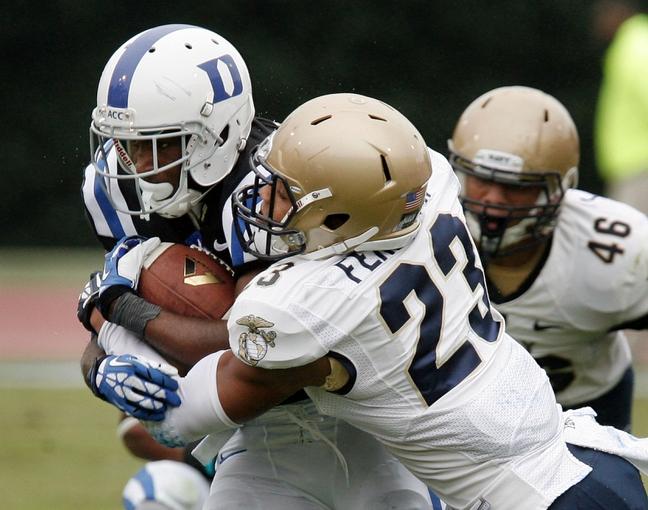 Oct 12, 2013; Durham, NC, USA; Navy Midshipmen safety Chris Ferguson (23) tackles Duke Blue Devils wide receiver Jamison Crowder (3) at Wallace Wade Stadium. Mandatory Credit: Mark Dolejs-USA TODAY Sports