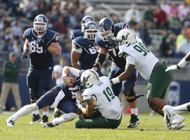 Oct 12, 2013; East Hartford, CT, USA; Connecticut Huskies quarterback Tim Boyle (14) is taken down by South Florida Bulls defensive lineman Aaron Lynch (19) in the second half at Rentschler Field. South Florida defeated Connecticut 13-10. Mandatory Credit: David Butler II-USA TODAY Sports