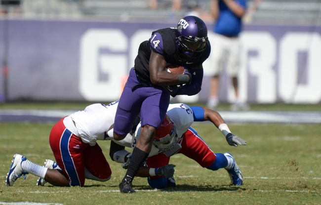 Oct 12, 2013; Fort Worth, TX, USA; TCU Horned Frogs receiver David Porter (14) eludes Kansas Jayhawks cornerback Dexter McDonald (12) and safety Cassius Sendish (33) to score on a 75-yard touchdown reception in the third quarter at Amon G. Carter Stadium. TCU defeated Kansas 27-17. Mandatory Credit: Kirby Lee-USA TODAY Sports