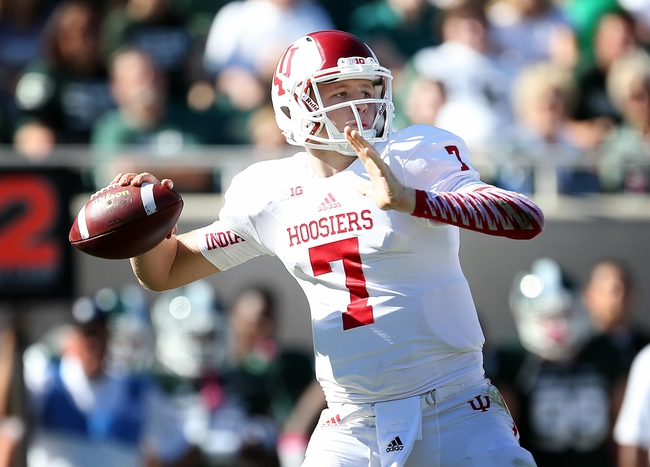 Oct 12, 2013; East Lansing, MI, USA; Indiana Hoosiers quarterback Nate Sudfeld (7) drops back to pass against Michigan State Spartans defense during the second half in a game at Spartan Stadium. MSU won 42-28. Mandatory Credit: Mike Carter-USA TODAY Sports