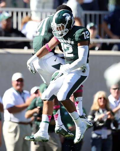 Oct 12, 2013; East Lansing, MI, USA; Michigan State Spartans running back R.J. Shelton (12) and  wide receiver Andre Sims Jr. (21) celebrate a touchdown against Indiana Hoosiers during the second half in a game at Spartan Stadium. MSU won 42-28. Mandatory Credit: Mike Carter-USA TODAY Sports