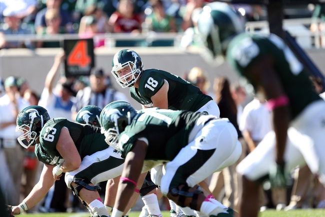Oct 12, 2013; East Lansing, MI, USA; Michigan State Spartans quarterback Connor Cook (18) prepares to take the snap of the ball from offensive linesman Jack Allen (66) during the second half in a game at Spartan Stadium. MSU won 42-28. Mandatory Credit: Mike Carter-USA TODAY Sports