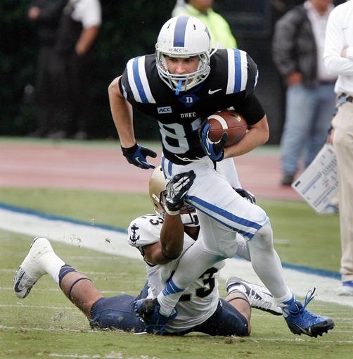 Oct 12, 2013; Durham, NC, USA; Navy Midshipmen safety Chris Ferguson (23) tackles Duke Blue Devils wide receiver Max McCaffrey (87) in their game at Wallace Wade Stadium. Mandatory Credit: Mark Dolejs-USA TODAY Sports