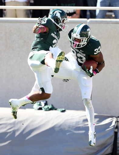 Oct 12, 2013; East Lansing, MI, USA; Michigan State Spartans running back Jeremy Langford (33) and wide receiver Macgarrett Kings Jr. (3) celebrate a touchdown against Indiana Hoosiers during the second half in a game at Spartan Stadium. MSU won 42-28. Mandatory Credit: Mike Carter-USA TODAY Sports