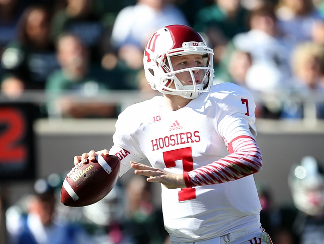Oct 12, 2013; East Lansing, MI, USA; Indiana Hoosiers quarterback Nate Sudfeld (7) drops back to pass against the Michigan State Spartans defense during the second half in a game at Spartan Stadium. MSU won 42-28. Mandatory Credit: Mike Carter-USA TODAY Sports