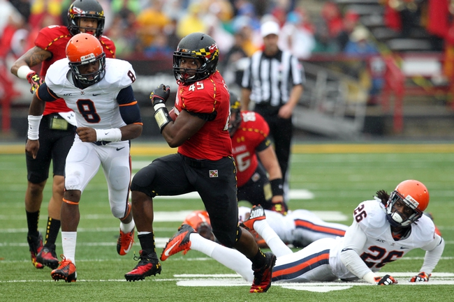 Oct 12, 2013; College Park, MD, USA; Maryland Terrapins running back Brandon Ross (45) runs past a diving Virginia Cavaliers cornerback Maurice Canady (26) and safety Anthony Harris (8) at Byrd Stadium. Mandatory Credit: Mitch Stringer-USA TODAY Sports