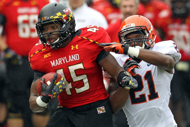 Oct 12, 2013; College Park, MD, USA; Maryland Terrapins running back Brandon Ross (45) tackled after a long gain by Virginia Cavaliers safety Brandon Phelps (21) at Byrd Stadium. Mandatory Credit: Mitch Stringer-USA TODAY Sports