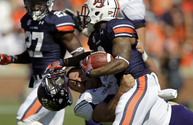 Oct 12, 2013; Auburn, AL, USA; Western Carolina Catamounts lineman Tyler Philpott (64) loses his helmet while trying to tackle Auburn Tigers defensive back Jonthanon Mincy (6) after an interception during the first half at Jordan Hare Stadium.  The Tigers beat the Catamounts 62-3.  Mandatory Credit: John Reed-USA TODAY Sports