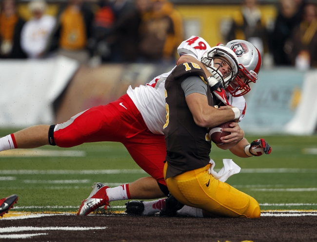 Oct 12, 2013; Laramie, WY, USA; Laramie, WY, USA; Wyoming Cowboys quarterback Brett Smith (16) is tackled by New Mexico Lobos linebacker Dakota Cox (49) during the first quarter at War Memorial Stadium. Mandatory Credit: Troy Babbitt-USA TODAY Sports