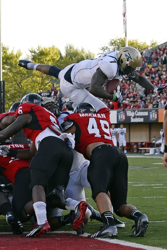 Oct 12, 2013; DeKalb, IL, USA; Akron Zips running back Jawon Chisholm (7) leaps into the end zone over Northern Illinois Huskies defensive end Jason Meehan (49) during the first quarter at Huskie Stadium. Mandatory Credit: Mike DiNovo-USA TODAY Sports