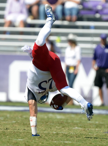 Oct 12, 2013; Fort Worth, TX, USA; Kansas Jayhawks receiver Brandon Bourbon (25) is upended against the TCU Horned Frogs at Amon G. Carter Stadium. TCU defeated Kansas 27-17. Mandatory Credit: Kirby Lee-USA TODAY Sports