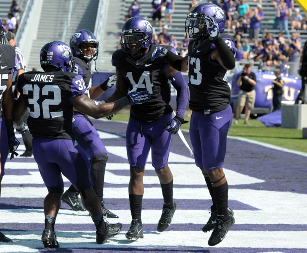 Oct 12, 2013; Fort Worth, TX, USA; TCU Horned Frogs receiver David Porter (14) celebrates with running backs Waymon James (32) and B.J. Catalon (23) after scoring a touchdown on a 75-yard reception in the third quarter against the Kansas Jayhawks at Amon G. Carter Stadium. TCU defeated Kansas 27-17. Mandatory Credit: Kirby Lee-USA TODAY Sports