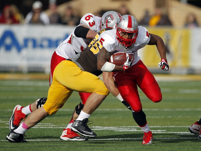 Oct 12, 2013; Laramie, WY, USA; Laramie, WY, USA; New Mexico Lobos running back Kasey Carrier (5) runs against Wyoming Cowboys defensive tackle Justin Bernthaler (96) during the third quarter at War Memorial Stadium. The Cowboys beat the Lobos 38-31. Mandatory Credit: Troy Babbitt-USA TODAY Sports