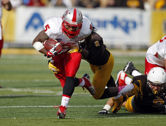 Oct 12, 2013; Laramie, WY, USA; Laramie, WY, USA; New Mexico Lobos running back Kasey Carrier (5) runs against Wyoming Cowboys safety Marqueston Huff (2) during the third quarter at War Memorial Stadium. The Cowboys beat the Lobos 38-31. Mandatory Credit: Troy Babbitt-USA TODAY Sports
