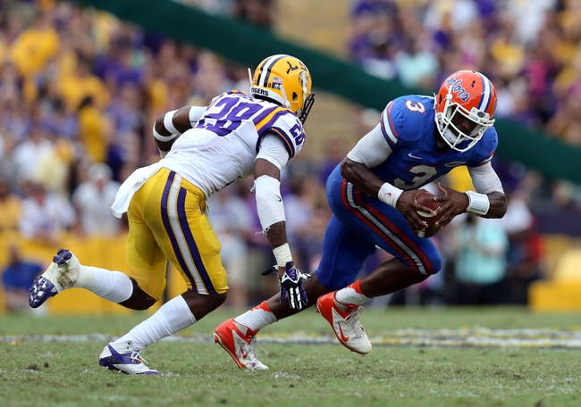 Oct 12, 2013; Baton Rouge, LA, USA; Florida Gators quarterback Tyler Murphy (3) tries to get away from LSU Tigers cornerback Jalen Mills (28) during the fourth quarter at Tiger Stadium. Mandatory Credit: Chuck Cook-USA TODAY Sports