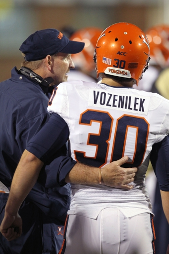 Oct 12, 2013; College Park, MD, USA; Virginia Cavaliers kicker Alec Vozenilek (30) is consoled by a coach on the sideline after missing what would have been a game winning filed goal in the closing seconds against the Maryland Terrapins at Byrd Stadium. Mandatory Credit: Mitch Stringer-USA TODAY Sports