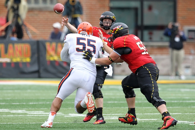 Oct 12, 2013; College Park, MD, USA; Maryland Terrapins quarterback Caleb Rowe (7) throws a pass under pressure from Virginia Cavaliers tackle David Dean (55) at Byrd Stadium. Mandatory Credit: Mitch Stringer-USA TODAY Sports