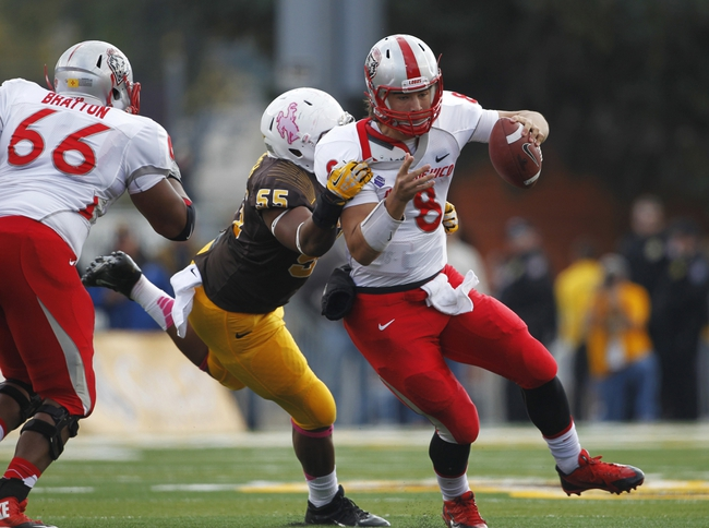 Oct 12, 2013; Laramie, WY, USA; Laramie, WY, USA; Wyoming Cowboys defensive end Eddie Yarbrough (55) tackles New Mexico Lobos quarterback Cole Gautsche (8) during the first quarter at War Memorial Stadium. The Cowboys beat the Lobos 38-31. Mandatory Credit: Troy Babbitt-USA TODAY Sports