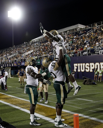 Oct 12, 2013; Miami, FL, USA; Alabama-Birmingham Blazers running back Darrin Reaves (5) celebrates his touchdown run with  offensive linesman Kaycee Ike (60) and tight end Tristan Henderson (88) against Florida International Panthers in the first quarter at FIU Stadium. Mandatory Credit: Robert Mayer-USA TODAY Sports