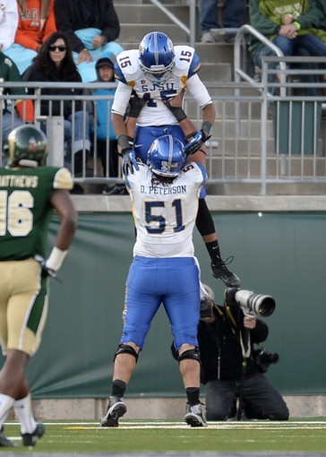 Oct 12, 2013; Fort Collins, CO, USA; San Jose State Spartans wide receiver Tyler Winston (15) is congratulated for his sixty four touchdown reception  by center David Peterson (51) in the fourth quarter against the Colorado State Rams at Hughes Stadium. The Spartans defeated the Rams 34-27. Mandatory Credit: Ron Chenoy-USA TODAY Sports