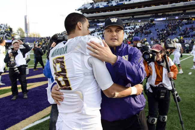 Oct 12, 2013; Seattle, WA, USA; Oregon Ducks quarterback Marcus Mariota (8) and Washington Huskies quarterback coach Marques Tuiasosopo hug after the game between the Washington Huskies and the Oregon Ducks at Husky Stadium. Oregon defeated Washington 45-24. Mandatory Credit: Steven Bisig-USA TODAY Sports