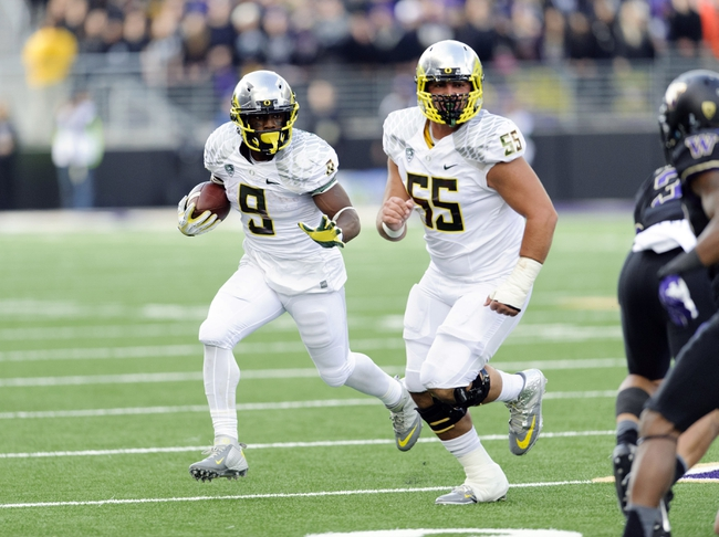 Oct 12, 2013; Seattle, WA, USA; Oregon Ducks running back Byron Marshall (9) carries the ball with offensive linesman Hroniss Grasu (55) blocking during the 2nd half against the Washington Huskies at Husky Stadium. Oregon defeated Washington 45-24. Mandatory Credit: Steven Bisig-USA TODAY Sports