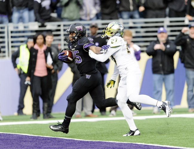 Oct 12, 2013; Seattle, WA, USA; Washington Huskies running back Bishop Sankey (25) stiff arms Oregon Ducks defensive back Terrance Mitchell (27) and scores a touchdown during the 2nd half at Husky Stadium. Oregon defeated Washington 45-24. Mandatory Credit: Steven Bisig-USA TODAY Sports