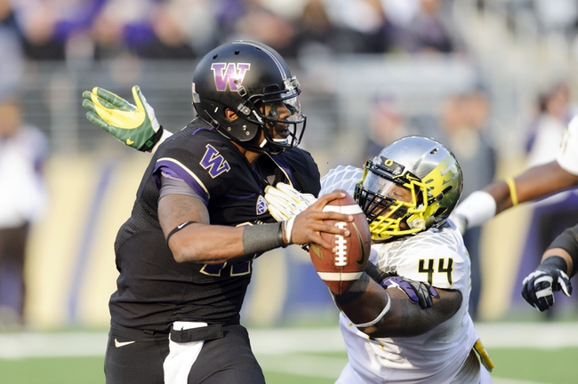 Oct 12, 2013; Seattle, WA, USA; Washington Huskies quarterback Keith Price (17) fights off the tackle by Oregon Ducks defensive lineman DeForest Buckner (44) during the 2nd half at Husky Stadium. Oregon defeated Washington 45-24. Mandatory Credit: Steven Bisig-USA TODAY Sports