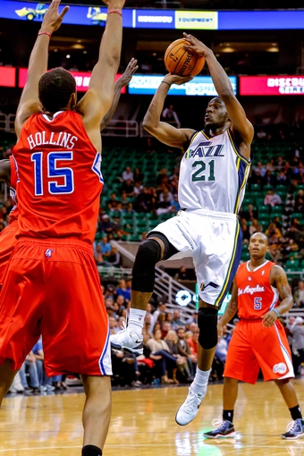 Oct 12, 2013; Salt Lake City, UT, USA; Utah Jazz shooting guard Ian Clark (21) shoots the ball over Los Angeles Clippers center Ryan Hollins (15) during the fourth quarter at EnergySolutions Arena. The Los Angeles Clippers won 106-74.  Mandatory Credit: Chris Nicoll-USA TODAY Sports