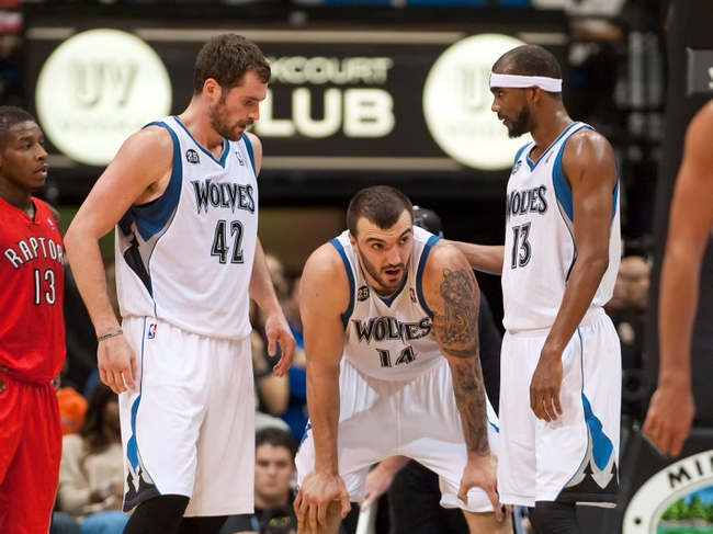 Oct 12, 2013; Minneapolis, MN, USA; Minnesota Timberwolves power forward Kevin Love (42) and small forward Corey Brewer (13) assist center Nikola Pekovic (14) who was knocked to the floor during the third quarter against the Toronto Raptors at Target Center. Raptors won 104-97. Mandatory Credit: Greg Smith-USA TODAY Sports