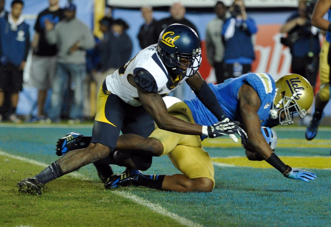Oct 12, 2013; Pasadena, CA, USA; UCLA Bruins wide receiver Shaquelle Evans (1) scores a fourth quarter touchdown after getting hit by California Golden Bears defensive back Isaac Lapite (20) at Rose Bowl.  Mandatory Credit: Robert Hanashiro-USA TODAY Sports