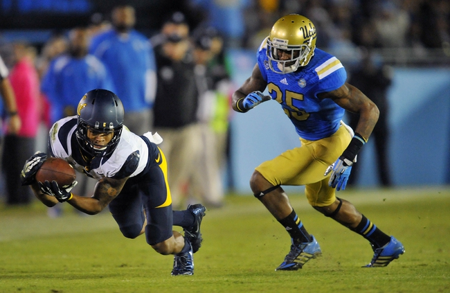 October 12, 2013; Pasadena, CA, USA; California Golden Bears wide receiver Bryce Treggs (1) catches a pass ahead of UCLA Bruins safety Brandon Sermons (25) during the second half at the Rose Bowl. Mandatory Credit: Gary A. Vasquez-USA TODAY Sports