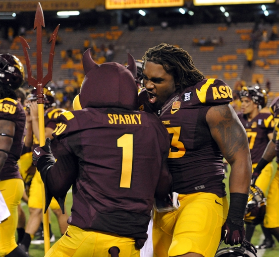 Oct 12, 2013; Tempe, AZ, USA; Arizona State Sun Devils mascot Sparky and defensive end Davon Coleman (43) celebrate after the game against the Colorado Buffaloes at Sun Devil Stadium. The Sun Devils beat the Buffaloes 54-13. Mandatory Credit: Casey Sapio-USA TODAY Sports