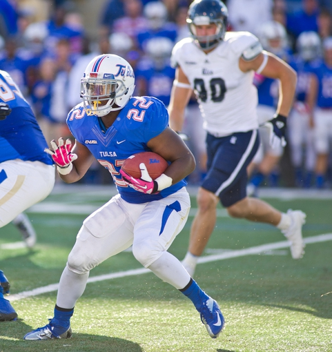 Oct 5, 2013; Tulsa, OK, USA; Tulsa Hurricanes running back Trey Watts (22) carries the ball as Rice Owls defensive end Cody Bauer (90) looks on during a game at Skelly Field at H.A. Chapman Stadium. Rice defeated Tulsa 30-27 in an overtime. Mandatory Credit: Beth Hall-USA TODAY Sports