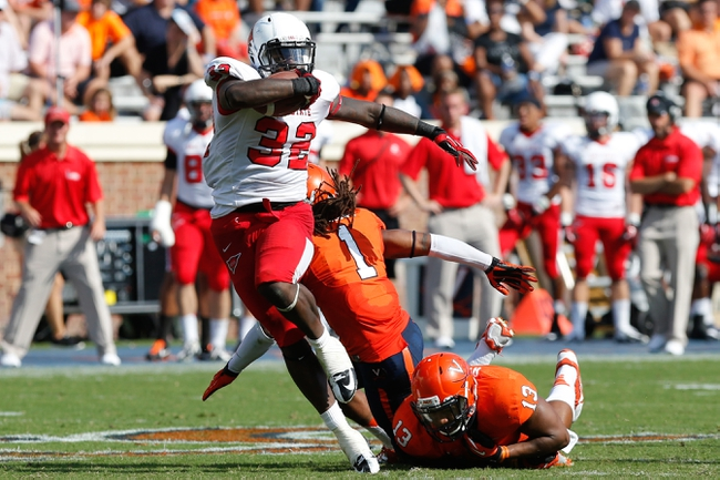 Oct 5, 2013; Charlottesville, VA, USA; Ball State Cardinals running back Jahwan Edwards (32) carries the ball as Virginia Cavaliers cornerback Demetrious Nicholson (1) and Cavaliers linebacker Daquan Romero (13) attempt the tackle at Scott Stadium. Mandatory Credit: Geoff Burke-USA TODAY Sports