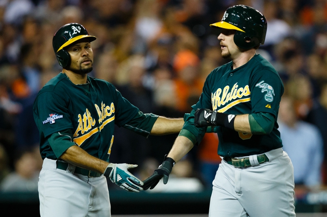 Oct 8, 2013; Detroit, MI, USA; Oakland Athletics center fielder Coco Crisp (4) and Oakland Athletics shortstop Jed Lowrie (8) congratulate each other after scoring in the ninth inning against the in game four of the American League divisional series at Comerica Park. Detroit won 8-6. Mandatory Credit: Rick Osentoski-USA TODAY Sports