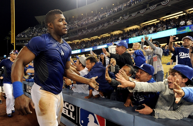 Oct 7, 2013; Los Angeles, CA, USA;  Los Angeles Dodgers right fielder Yasiel Puig (66) celebrates with fans after defeating the Atlanta Braves 3-2 in game four of the National League divisional series at Dodger Stadium. Dodgers won 4-3. Mandatory Credit: Jayne Kamin-Oncea-USA TODAY Sports