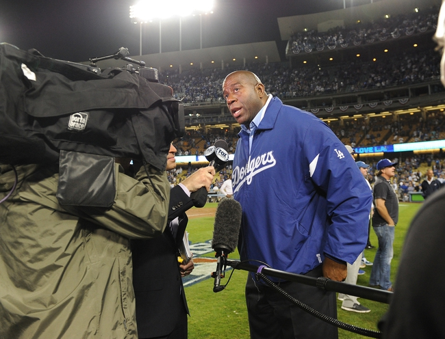 Oct 7, 2013; Los Angeles, CA, USA;  Los Angeles Dodgers owner Magic Johnson is interviewed after the the team defeated the Atlanta Braves 4-3 in game four of the National League divisional series at Dodger Stadium. Dodgers won 4-3. Mandatory Credit: Jayne Kamin-Oncea-USA TODAY Sports