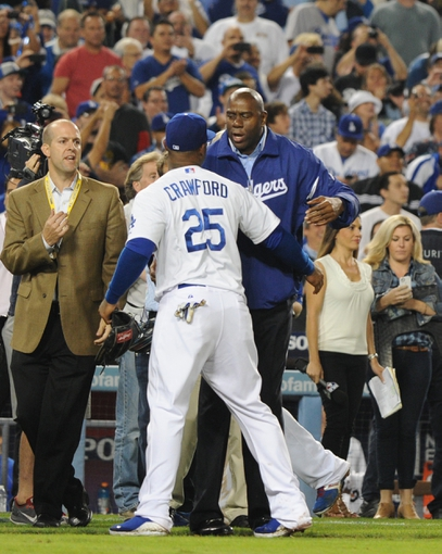 Oct 7, 2013; Los Angeles, CA, USA;  Los Angeles Dodgers owner Magic Johnson and Los Angeles Dodgers left fielder Carl Crawford (25) celebrate after defeating the Atlanta Braves 4-3 in game four of the National League divisional series at Dodger Stadium. Dodgers won 4-3. Mandatory Credit: Jayne Kamin-Oncea-USA TODAY Sports