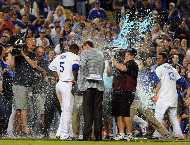 Oct 7, 2013; Los Angeles, CA, USA;  Los Angeles Dodgers third baseman Juan Uribe (5) is hit by water by Los Angeles Dodgers shortstop Hanley Ramirez (13) while being interviewed by reporter Craig Sager after defeating the Atlanta Braves 4-3 in game four of the National League divisional series at Dodger Stadium. Dodgers won 4-3. Mandatory Credit: Jayne Kamin-Oncea-USA TODAY Sports