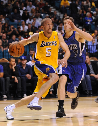 Oct 10, 2013; Las Vegas, NV, USA; Los Angeles Lakers guard Steve Blake (5) dribbles around Sacramento Kings guard Jimmer Fredette (7) during an NBA preseason game at MGM Grand Arena. The Kings won the game 104-86. Mandatory Credit: Stephen R. Sylvanie-USA TODAY Sports