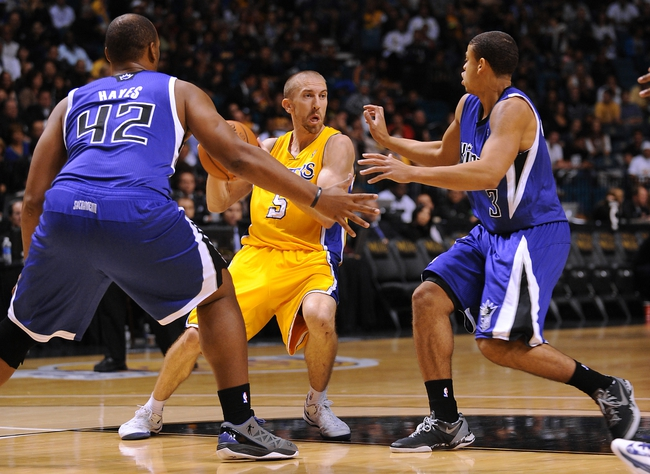 Oct 10, 2013; Las Vegas, NV, USA; Los Angeles Lakers guard Steve Blake (5) protects the ball while being defended by Sacramento Kings forward Chuck Hayes (42) and guard Ray McCallum (3) during an NBA preseason game at MGM Grand Arena. The Kings won the game 104-86. Mandatory Credit: Stephen R. Sylvanie-USA TODAY Sports