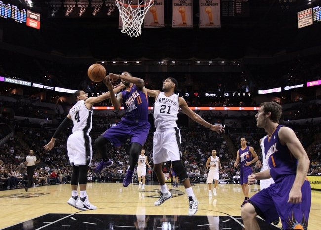 Oct 13, 2013; San Antonio, TX, USA; Phoenix Suns  forward Markieff Morris (11) loses control of the ball while driving to the basket as San Antonio Spurs guard Danny Green (4) and forward Tim Duncan (21) defend during the first half at AT&T Center. Mandatory Credit: Soobum Im-USA TODAY Sports