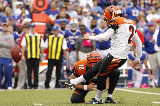 Oct 13, 2013; Orchard Park, NY, USA; Cincinnati Bengals kicker Mike Nugent (2) kicks the winning field goal as punter Kevin Huber (10) holds during overtime against the Buffalo Bills at Ralph Wilson Stadium. Mandatory Credit: Kevin Hoffman-USA TODAY Sports