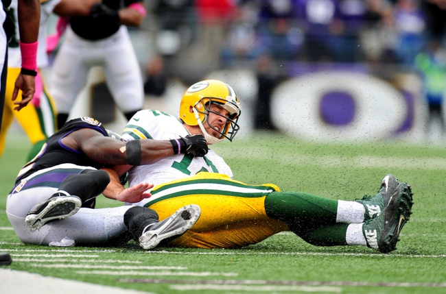 Oct 13, 2013; Baltimore, MD, USA; Green Bay Packers quarterback Aaron Rodgers (12) is tackled by Baltimore Ravens safety James Ihedigbo (32) at M&T Bank Stadium. Mandatory Credit: Evan Habeeb-USA TODAY Sports