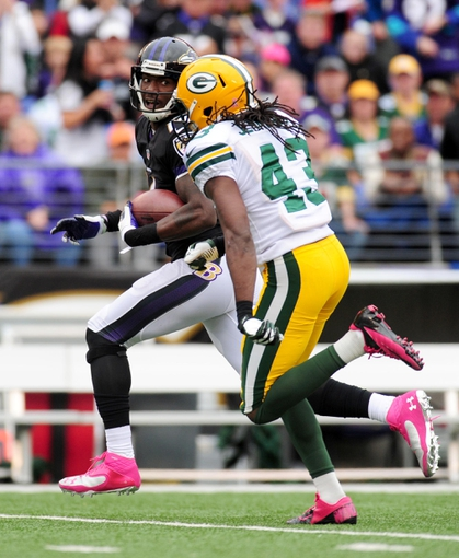 Oct 13, 2013; Baltimore, MD, USA; Baltimore Ravens wide receiver Marlon Brown (14) runs with the ball past Green Bay Packers safety M.D. Jennings (43) at M&T Bank Stadium. Mandatory Credit: Evan Habeeb-USA TODAY Sports