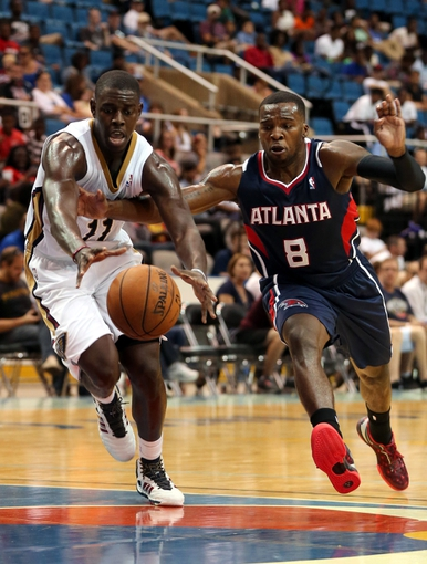 Oct 13, 2013; Biloxi, MS, USA; New Orleans Pelicans point guard Jrue Holiday (11) and Atlanta Hawks point guard Shelvin Mack (8) lunge for a loose ball during the second half of their game at the Mississippi Coast Coliseum. The Pelicans won 105-73. Mandatory Credit: Chuck Cook-USA TODAY Sports