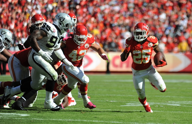 Oct 13, 2013; Kansas City, MO, USA; Kansas City Chiefs running back Jamaal Charles (25) runs the ball as Oakland Raiders linebacker Kaelin Burnett (95) attempts the tackle during the second half at Arrowhead Stadium. The Chiefs won 24-7. Mandatory Credit: Denny Medley-USA TODAY Sports